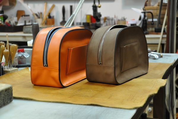 Finising of the slices bag : hue, hot net and polishing of slices. Luxury leather goods craftsmen in France. LE NOËN