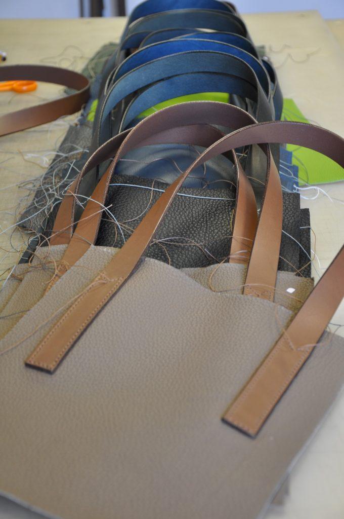 Les poignées sont montées en premier sur la face du sac en cuir. Fabrication  LE dbfabb1bac0