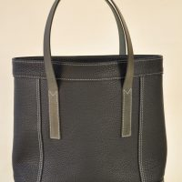 Black woman's bag made with taurillon leather, lined with black cotton. It closes with two press stud. French luxury leather goods by LE NOËN.