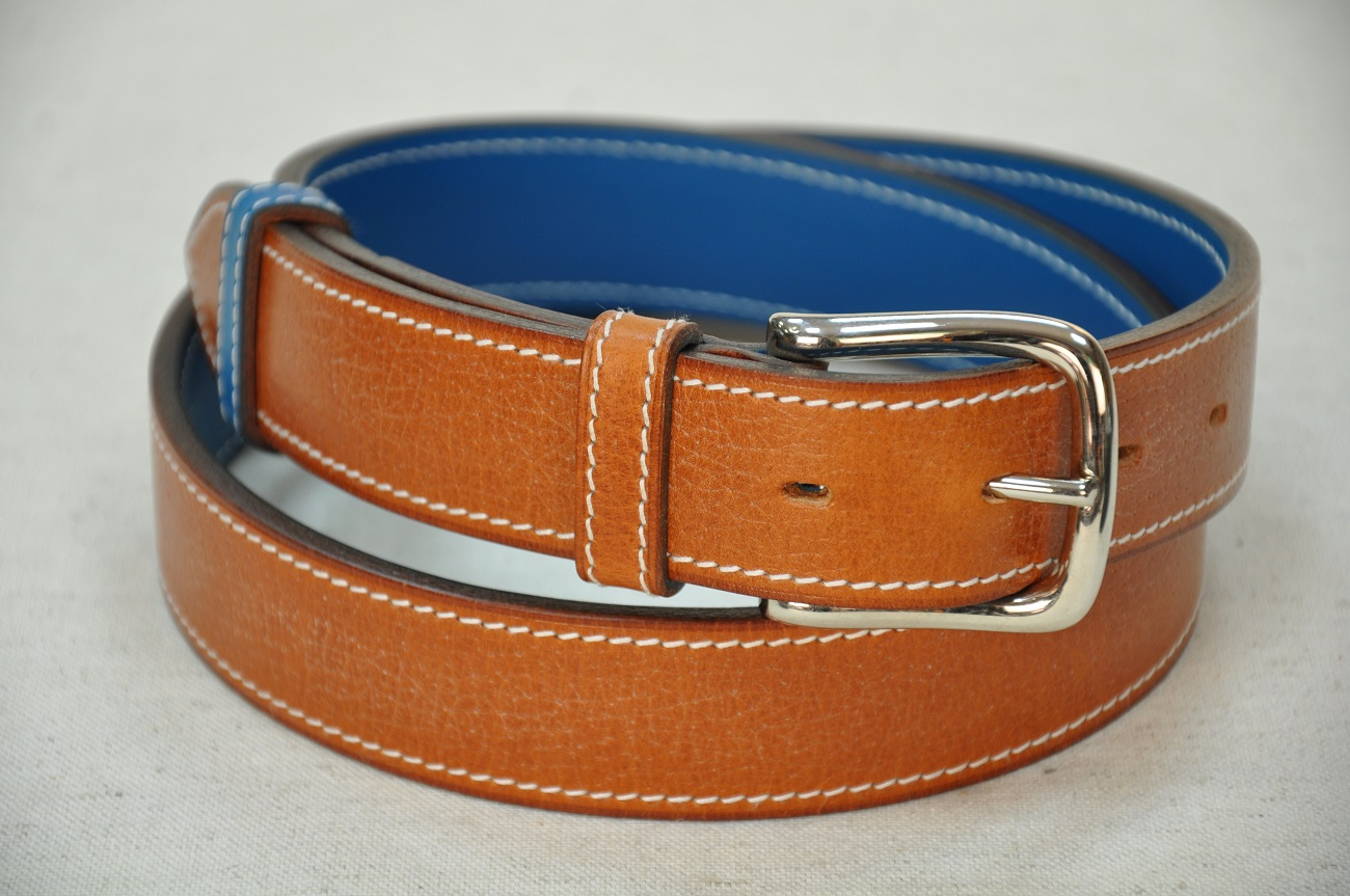 Cowhide belt pig grained, lined with blue calfskin. Solid brass buckle, nickel-plated finish. Made in France by leather goods makers.