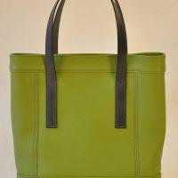 Le sac Valentine est en taurillon vert anis, ses poignées sont en vachette à tannage végétal bleu gris foncé. Design et fabrication française des maroquiniers du luxe LE NOËN.