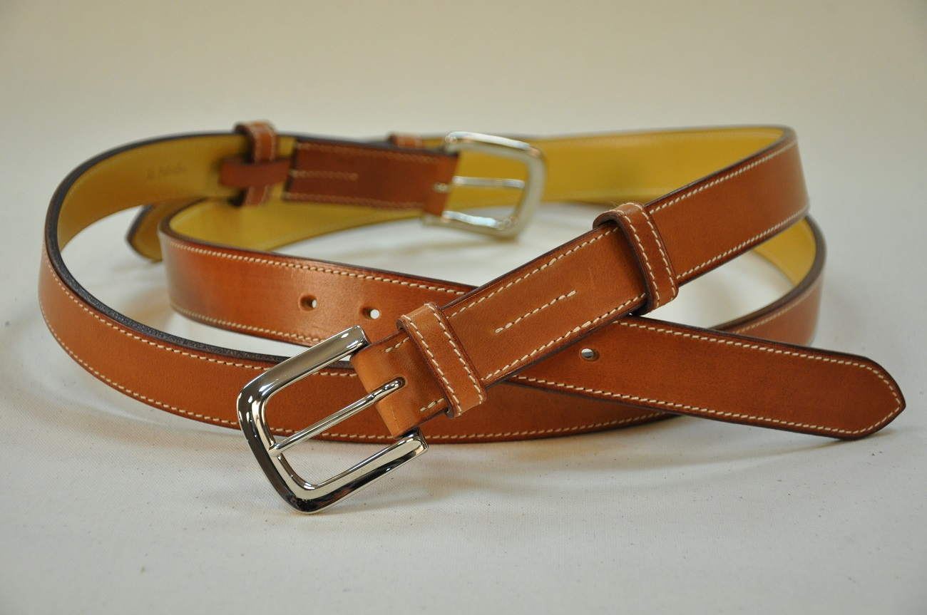 Stirrups style belts in vegetable tanned cowhide with solid brass buckle, nickel-plated finish. French leather goods designer. LE NOËN in France