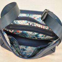 La besace en taurillon bleu est doublé en tissu avec un aménagement de poches. le fond du sac est doublé en cuir. Création LE NOËN maroquiniers du luxe français.